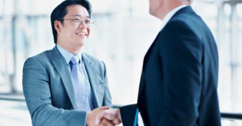 chinese_businessman_shaking_hands_with_caucasian_businessman